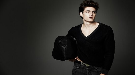 Male Fashion model dressed in black with handbag